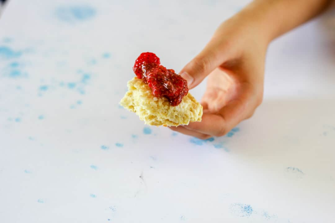 Torn bite of orange rosewater scone topped with strawberry chia compote.