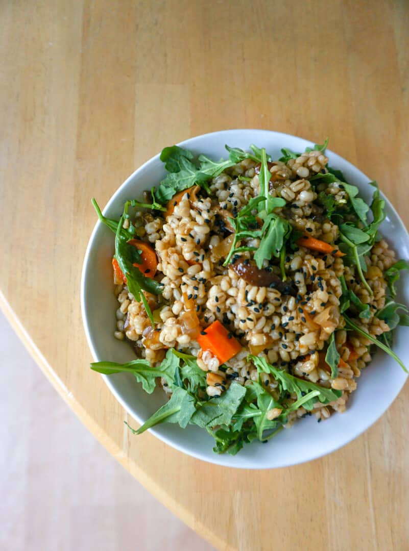 Nubs of brown barley, broken up by chopped carrots and arugula leaves.