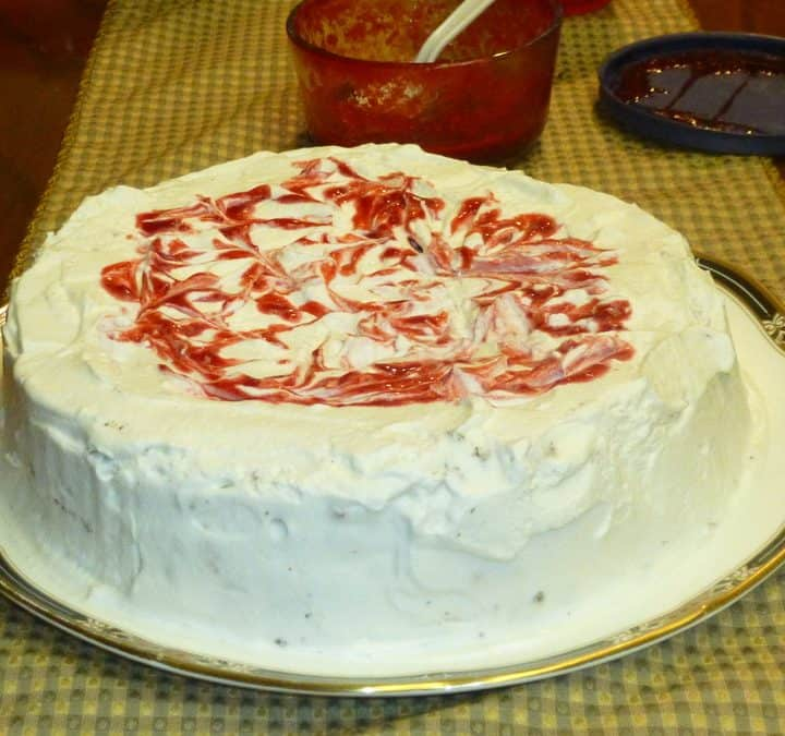 This Chocolate Meringue Cake with Whipped Cream and Raspberries features chocolate cakes with meringue baked in, then layered with whipped cream and served with raspberry sauce.