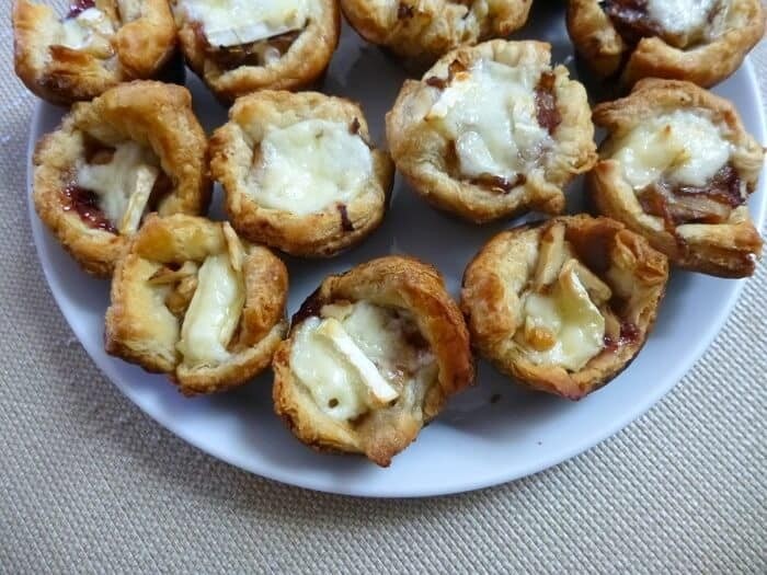 You can also make mini caramelized onion and brie tarts by using a mini muffin pan. I personally like the big version better, since the topping to crust ratio is higher and better, but both ways are delicious. #caramelizedonions #brie #puffpastry #appetizer