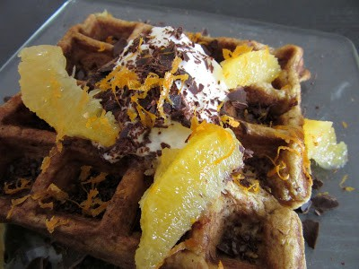 This pumpkin spice waffle is topped with yogurt, orange zest, orange segments and shaved chocolate. #pumpkinspice #waffles #oranges #chocolate