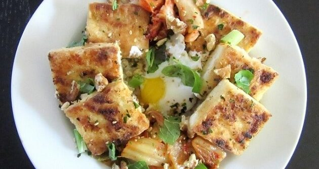This spicy pan-fried tofu rice bowl has everything you could ever want: crispy tofu, crunchy kimchi, runny eggs and fresh herbs. #tofu #ricebowl #kimchi #eggs
