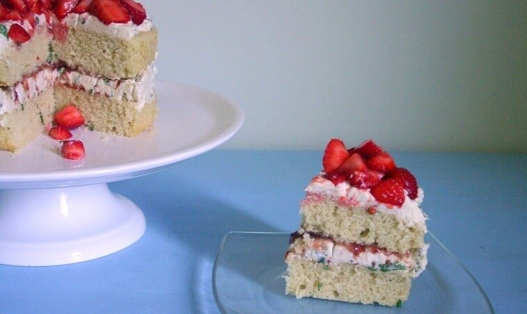 A slice taken out of this strawberry lemonade cake with fresh mint buttercream. #strawberry #lemon #mint #cake