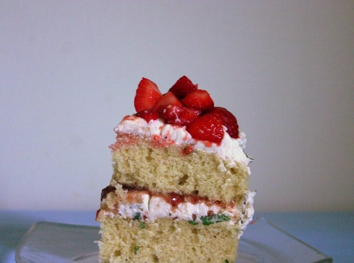 The cross section of a piece of this strawberry lemonade cake with fresh mint buttercream features cake, ruby red strawberry preserves and mint-flecked buttercream. #strawberry #lemon #mint #cake
