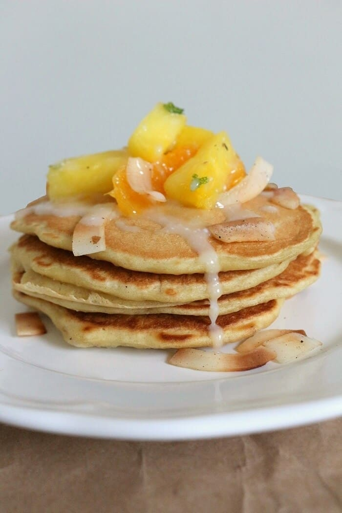 These double coconut pancakes with pineapple orange salad are drizzled with an easy coconut glaze made of coconut milk and powdered sugar. #coconut #pancakes #pineapple #breakfast #brunch