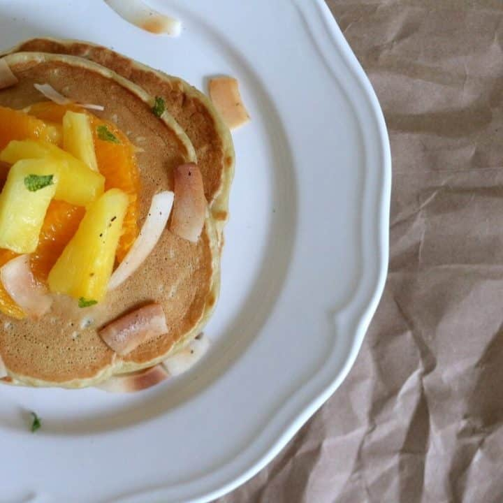 These double coconut pancakes with pineapple orange salad get a double hit of coconut from the toasted coconut and coconut glaze on top. #coconut #pancakes #pineapple #breakfast #brunch