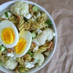 This weeknight cauliflower pasta with pecans and feta is also topped with a hardboiled egg, and a generous sprinkling of scallions.