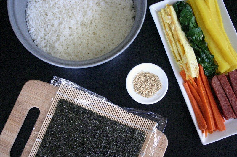 The set-up for making spam kimbap: a pot of rice, a sheet of seaweed on top of a sushi rolling mat, some sesame seeds, and allllll the fillings. #spam #kimbap #korean #sushi