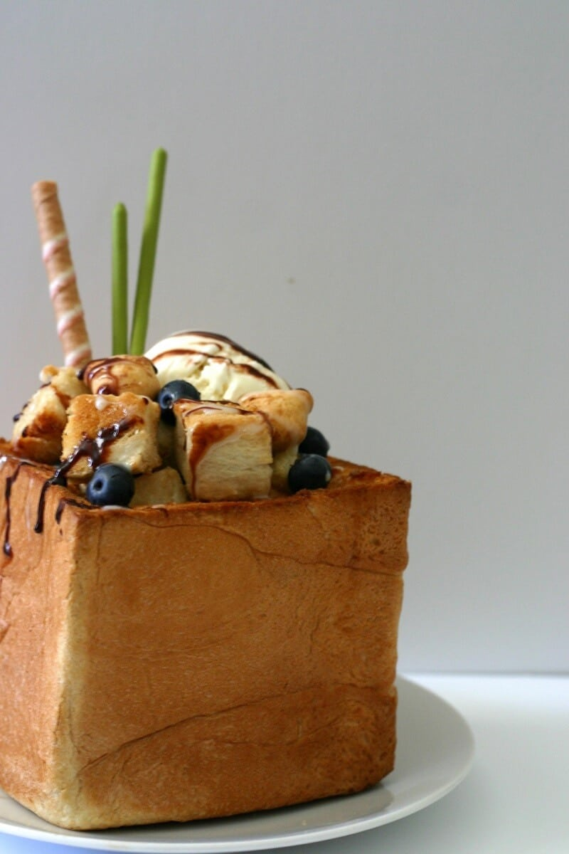 Close-up of all the fillings in this honey toast: ice cream, blueberries, cubed toast, matcha Pocky, cigar cookies and chocolate sauce. #honey #toast #icecream #dessert