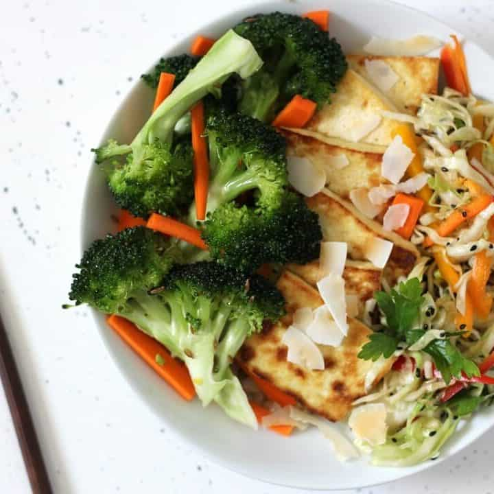 This coconut rice bowl with cumin broccoli slaw and quick pickles is the kind of lunch that makes you happy to have a bowl full of vegetables. #lunchideas #ricebowl #quickpickles #tofu #vegetables