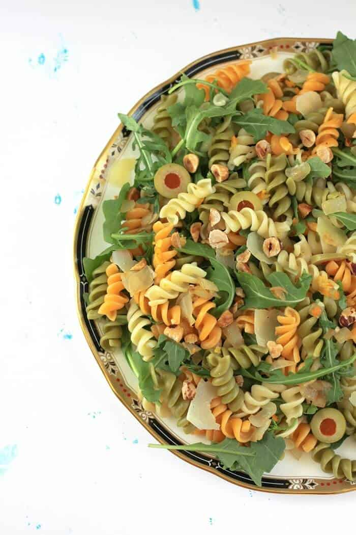 This olive pasta with kumquat vinaigrette is packed with goodies: olives, parmesan, arugula and toasted hazelnuts. #olives #pasta #pastasalad #arugula #preservedlemon