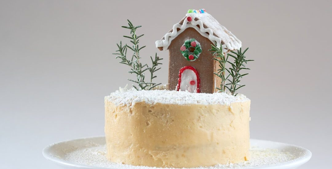 This white peppermint cake is decorated with a mini gingerbread house, rosemary sprigs, ground coconut and powdered sugar, but you can do whatever you like. #peppermint #layercake #swissmeringuebuttercream #dessert #gingerbreadhouse