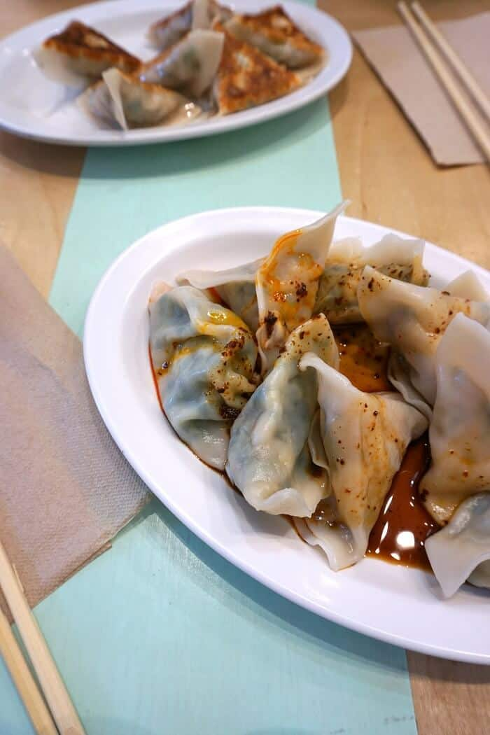 Cozy up to tasty pork dumplings drenched in spicy sweet sauce if you're in NYC in January! #dumplings #potstickers #gyoza #lunchtime