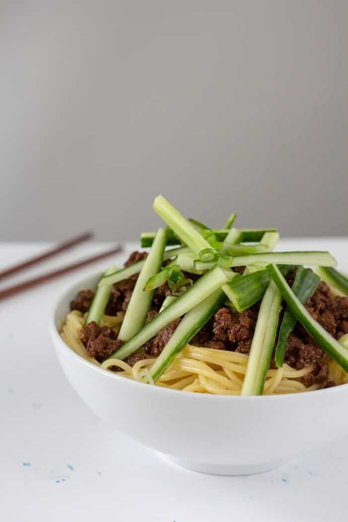 Top a big bowl of rich zha jiang mian (think a pork or beef ragu flavored with some sweet bean sauce) with plenty of cucumber and green onions to keep it fresh. #chinese #asian #noodles