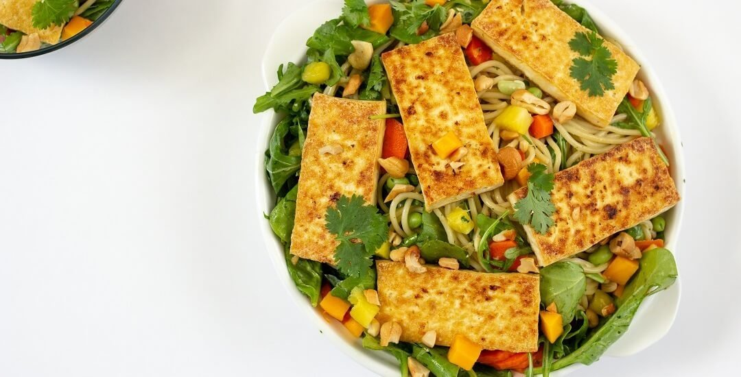 Bowl of pasta and arugula, topped with pan-fried tofu slabs.