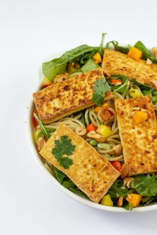 Pasta salad with fruit, tossed with cilantro coconut milk dressing and topped with golden-brown crispy tofu.