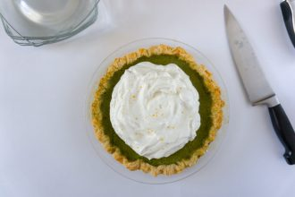 Green tea pie topped with whipped cream with serving utensils and plates.