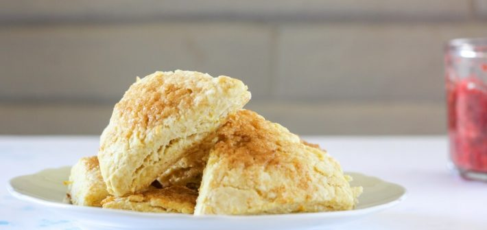 Stack of orange rosewater scones in front of a white brick wall.
