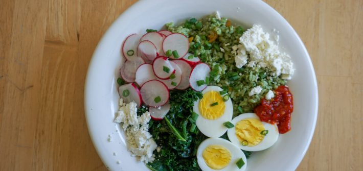 A bowl filled with bright green kale pesto dressed rice, white feta cheese, red hot sauce, halved hard-boiled egg and white/pink radishes.
