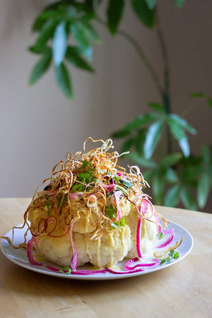 A whole head of roasted cauliflower, topped with crispy shoestring potatoes, pickled onions and plenty of hollandaise sauce.