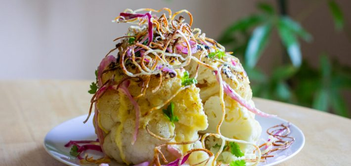 Slice cut out from whole roasted cauliflower, topped with purple onions, yellow hollandaise, golden crispy potatoes and cilantro leaves.