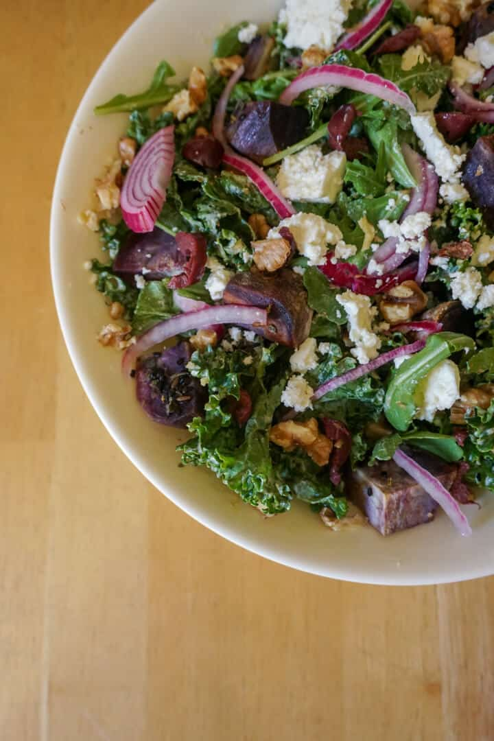 This salad is full of emerald hued kale, purple sweet potatoes, crumbled feta and pickled red onion.