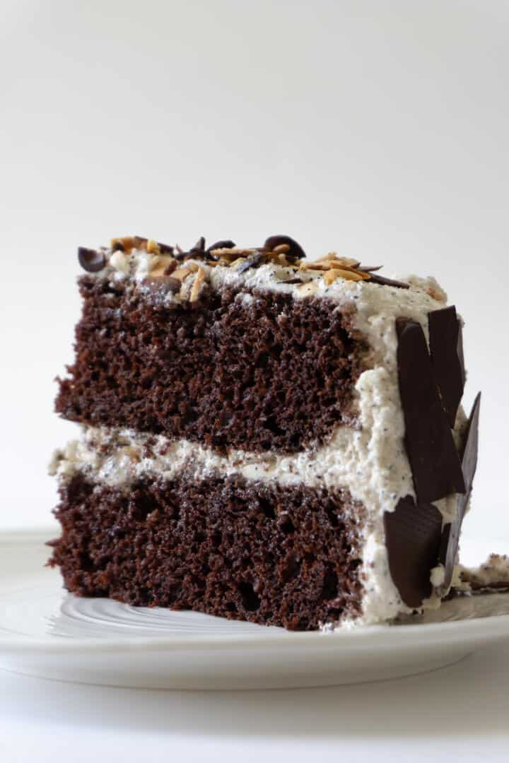 A chocolate layer cake filled with buttercream and decorated with coffee-glazed almonds and dark chocolate shards.