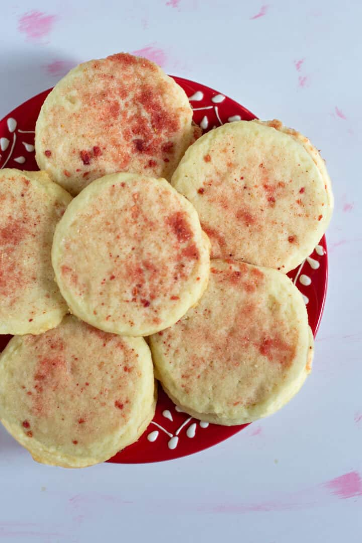 These pale cream-colored sugar cookies are dusted with bright pink crushed freeze-dried strawberries and sugar.