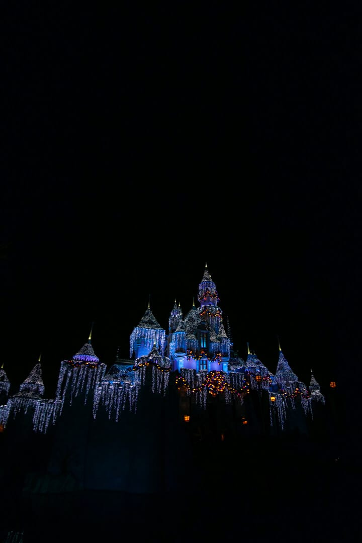 Blue lights lit up at night time on Sleeping Beauty's Castle in Disneyland.