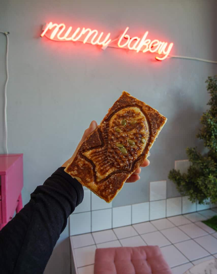 Hand holding rectangular fish imprinted croissant filled with brown sugar and nuts from Mumu Bakery in Koreatown, Los Angeles.