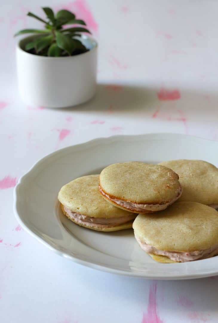 These strawberry sandwich cookies have buttery crispy edged cookies filled with pale pink strawberry cream.