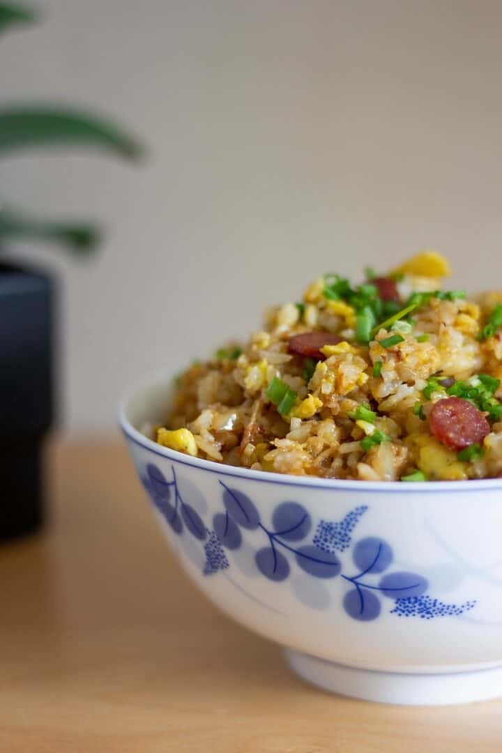 A big bowl of salted fish fried rice, which chunks of pale yellow scrambled eggs, chopped green onions and crispy golden nuggets of lap cheong (sausage).