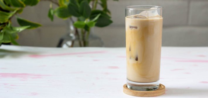 Glass of pale tan coffee milk tea with ice cubes.
