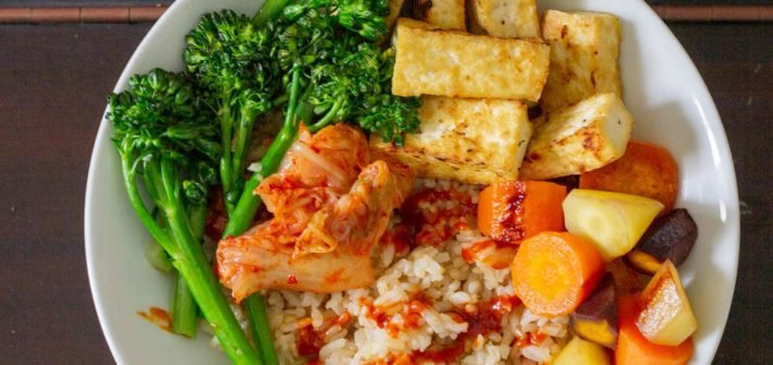Bowl with rice, tofu, broccolini, kimchi, carrots and gochujang sauce.