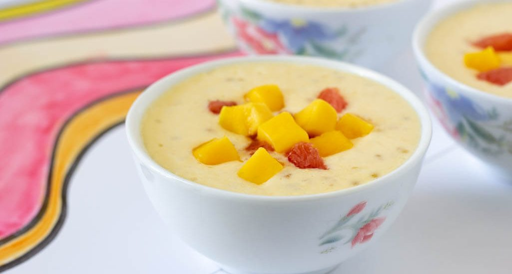 A white bowl filled with pale yellow mango coconut smoothie topped with mango and pomelo chunks.