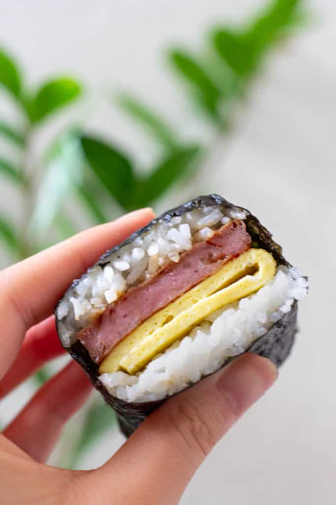 Hand holding a slice of spam musubi with egg.