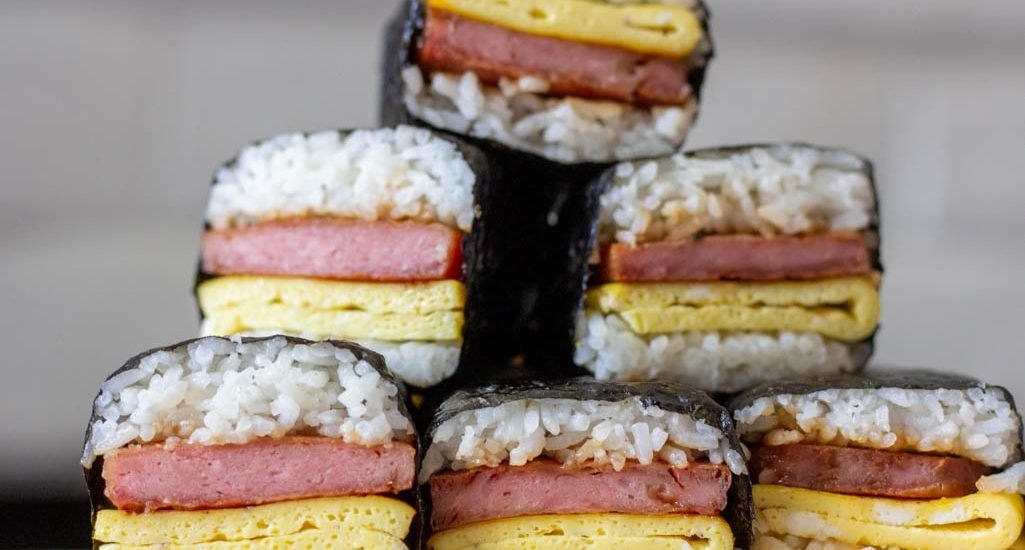 Stack of 6 spam musubi with egg on a wooden cutting board.