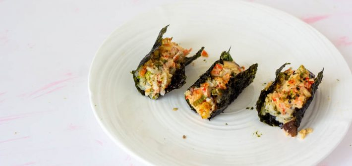 Three little packages of spoonfuls of rice topped with imitation crab salad, tucked into crispy seaweed.