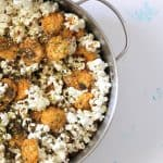 Pot full of popcorn topped with crispy golden brown crackers and dark green furikake.