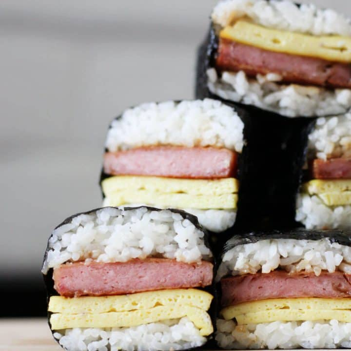 Stack of spam musubi with egg on a wooden cutting board.