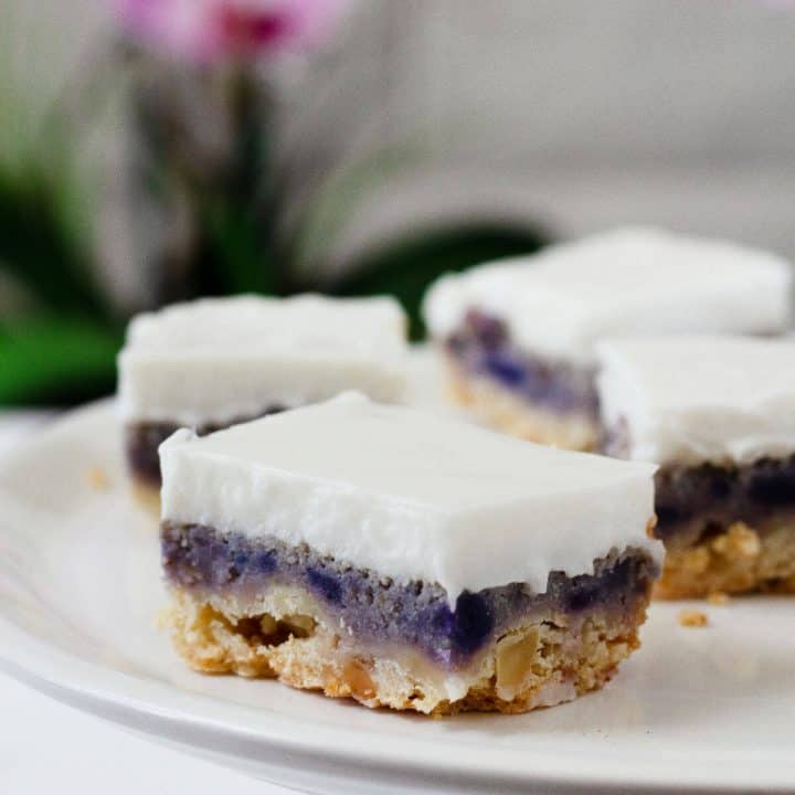 Three layer pie bars with a golden brown shortbread crust, bright purple sweet potato filling and creamy white coconut topping.