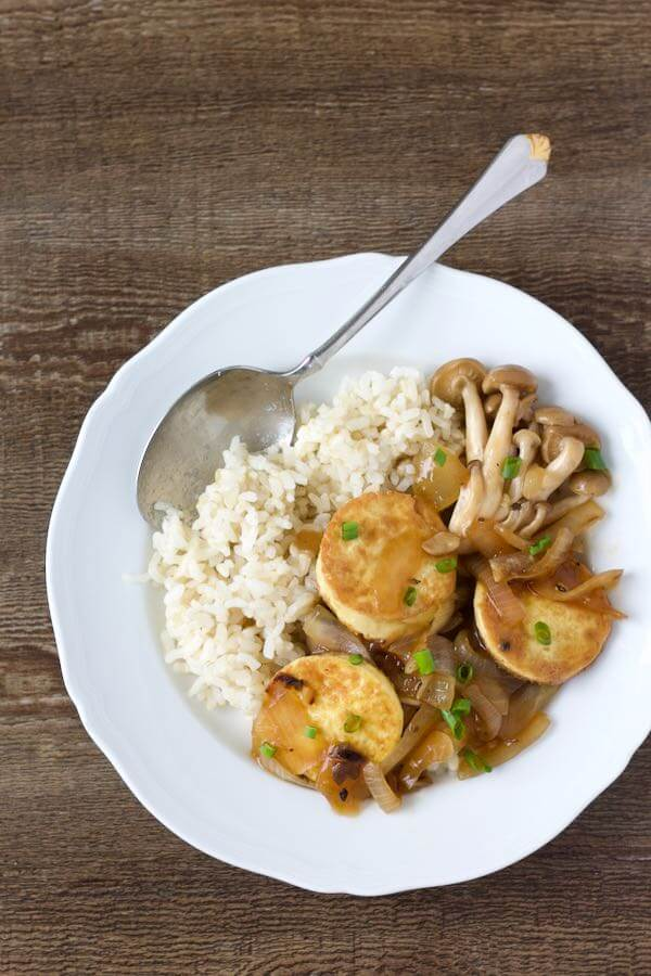 White plate with brown rice, circles of pan-fried tofu and mushrooms.