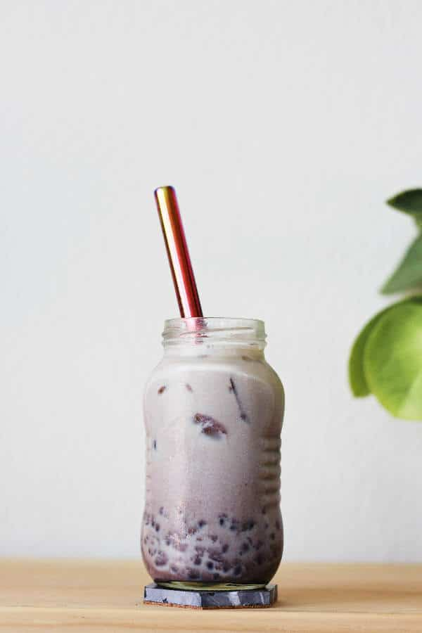 Small glass jar full of ombre maroon liquid, with the light colored milk tea at the top and maroon-colored sweet red bean at the bottom.