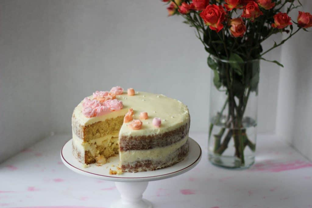 White cake decorated with pink icing flowers with a slice cut out of it.