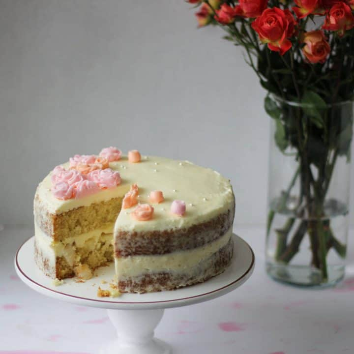 Cake on a cake stand with a slice cut out, showing the pale tan cake and chopped lychees on the inside.
