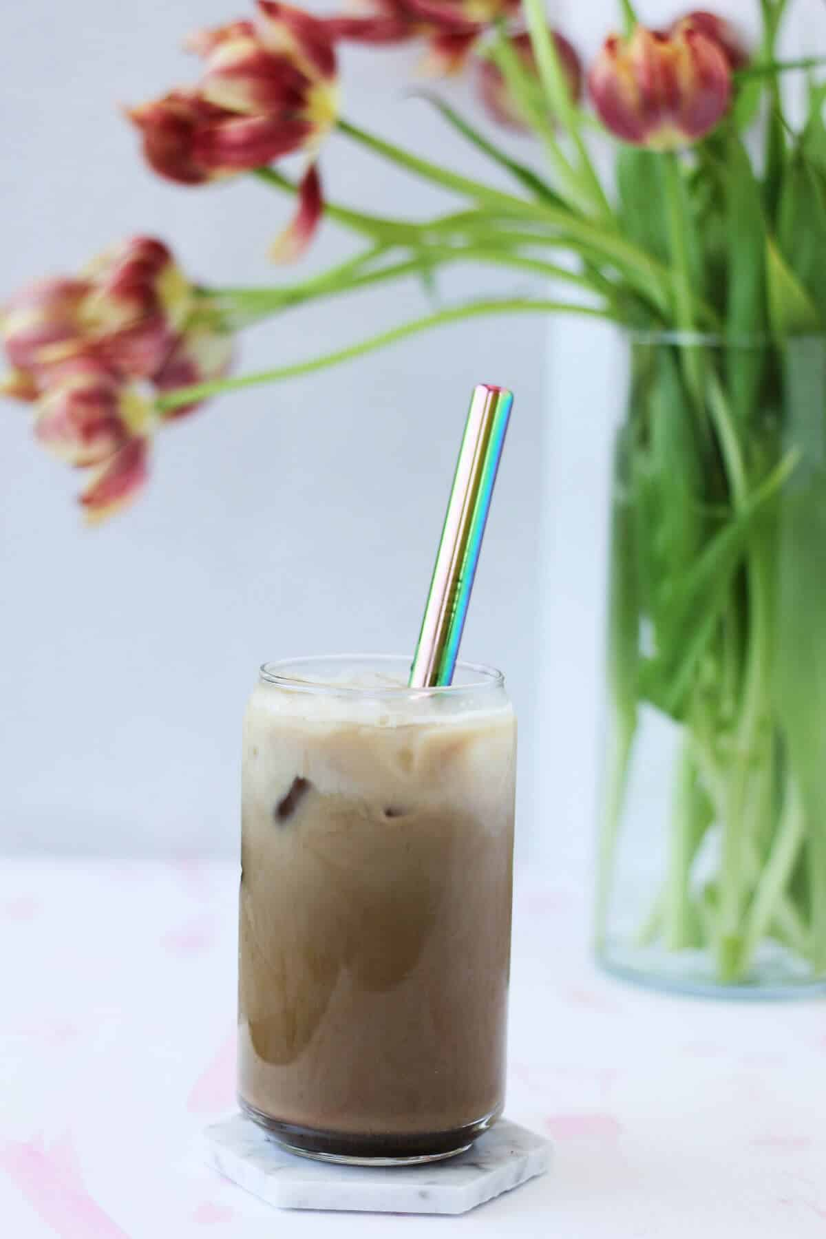 Clear glass filled with beige coffee, ice and a metal straw in front of a vase filled with pink and red flowers.