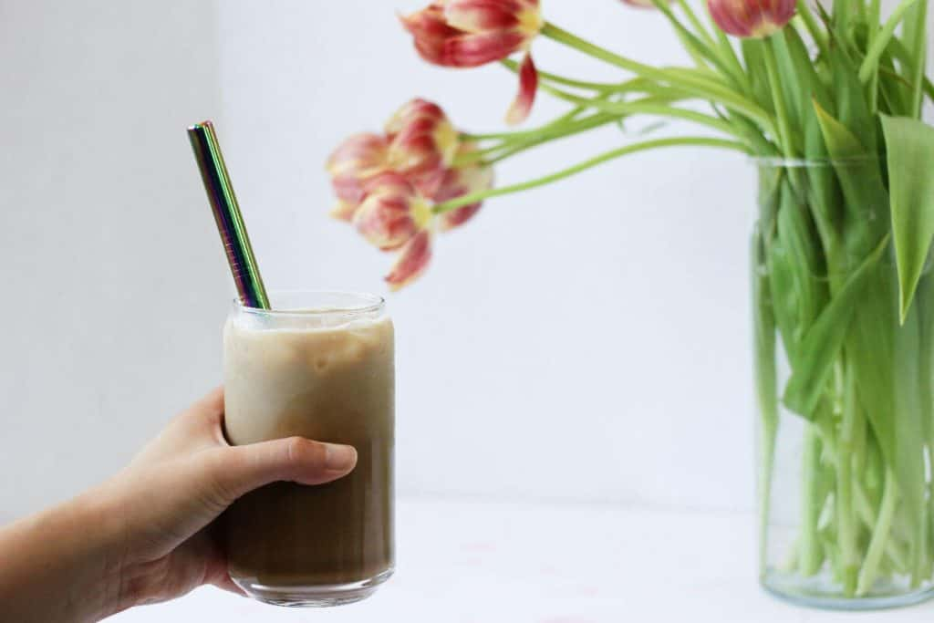 Hand holding a glass of iced coffee in front of a vase of red and pink flowers.