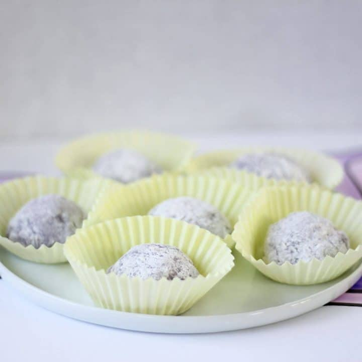 White plate under yellow cupcake wrappers holding cornstarch-dusted purple mochi balls.
