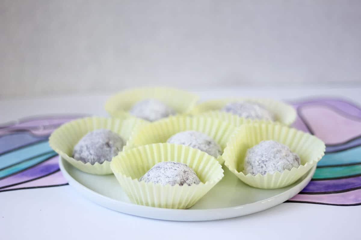 Plate with purple mochi in yellow cupcake wrappers.