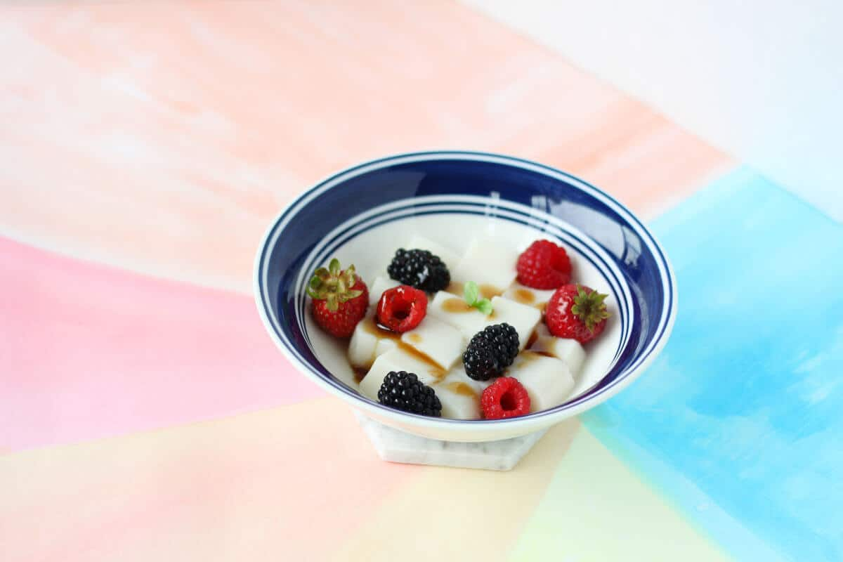 White and blue bowl filled with cubes of white almond tofu, topped with berries and brown sugar syrup.